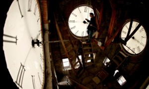 Custodian Ray Keen changes the time to daylight savings time on the 100-year-old clock on the Clay C